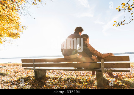 Couple sitting on bench, rear view - Stock Photo