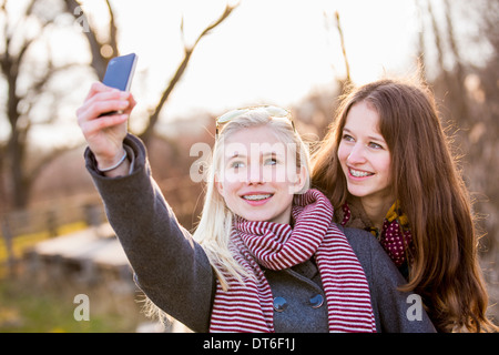 Teenage girls photographing themselves with smartphone - Stock Photo