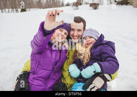 Mother and Father with daughter taking family portrait with mobile phone - Stock Photo