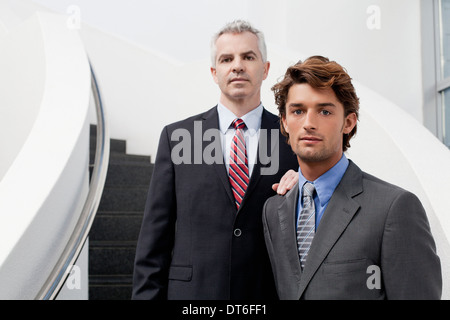 Portrait of two businessmen on office stairs - Stock Photo