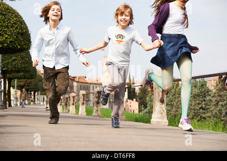 Sister and younger brothers running through park, Province of Venice, Italy - Stock Photo