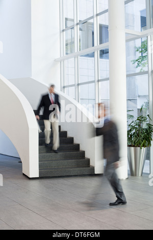 Businessmen on the move in office atrium - Stock Photo