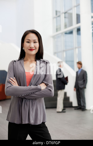 Portrait of young businesswoman in office atrium - Stock Photo