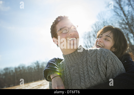 Two people, a man and a woman hugging each other and laughing. A walk on a winter day.