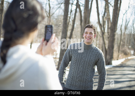 A couple outdoors on a snowy day. A woman holding a camera phone, taking photographs of a man. - Stock Photo