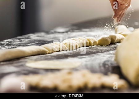 Chef's hand sprinkling flour on gnocchi in commercial kitchen - Stock Photo