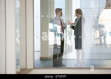 Business colleagues in discussion through glass - Stock Photo