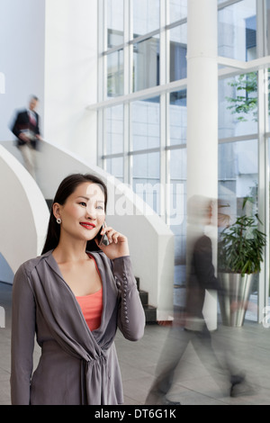 Businesswoman using cellphone in office atrium - Stock Photo