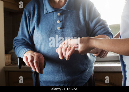 Personal care assistant supporting senior woman to walk - Stock Photo