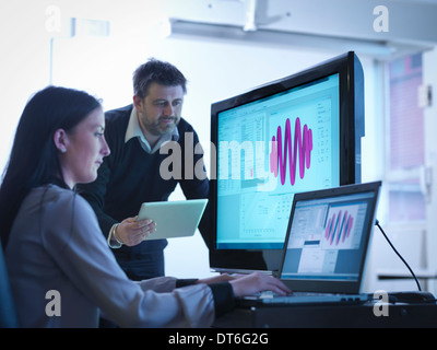 Workers using software to calibrate springs in office - Stock Photo
