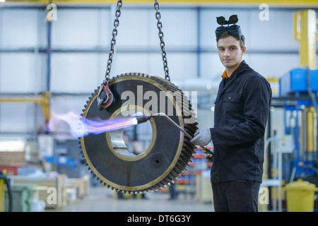 Portrait of engineer heat treating industrial gear in factory - Stock Photo
