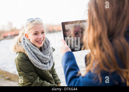 Teenage girl photographing friend with digital tablet Stock Photo
