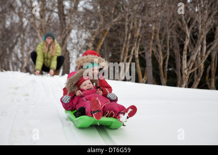 Mother watching two young daughters sledging in snow - Stock Photo