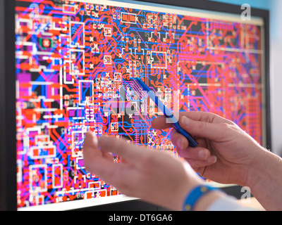 Engineer points to computer screen with electronic circuitry designs for automotive use - Stock Photo