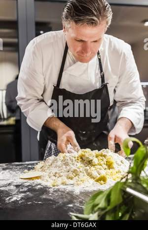 Chef mixing gnocchi dough in commercial kitchen - Stock Photo