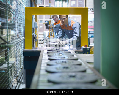 Workers on production line in industrial clutch factory - Stock Photo