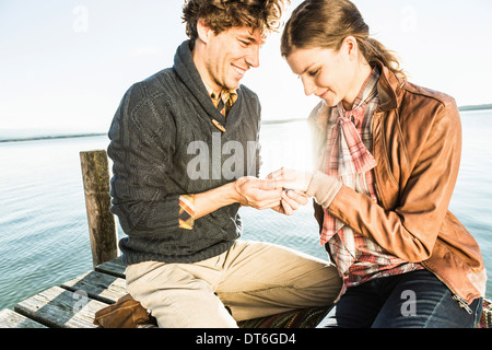 Man putting engagement ring on woman - Stock Photo