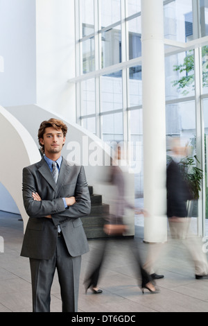 Portrait of young businessman in office atrium - Stock Photo