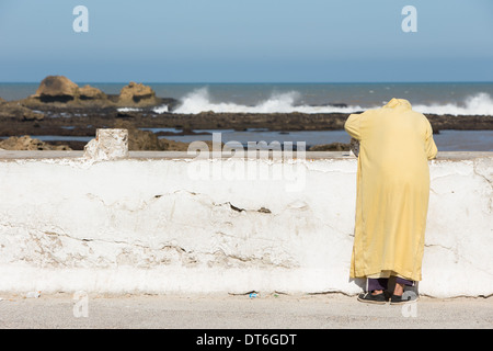 Old man in yellow robes watching the waves crashing on the rocks - Stock Photo