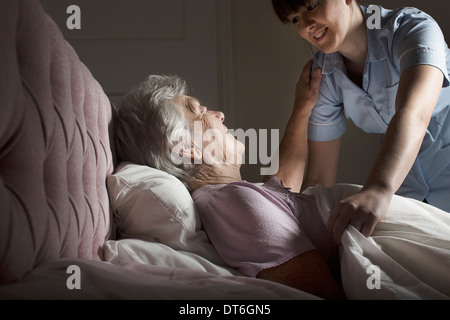 Personal care assistant chatting to senior woman in bed - Stock Photo