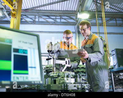 Engineer and apprentice using digital tablet at work station in factory - Stock Photo
