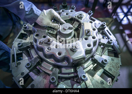Close up of engineer assembling industrial clutch on production line - Stock Photo