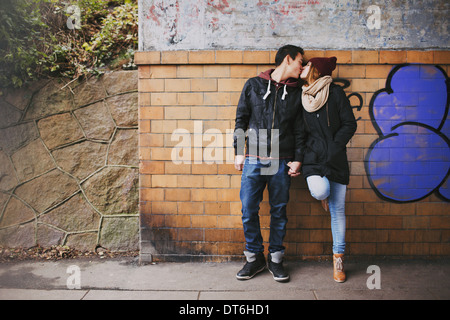 Affectionate teenage couple kissing outdoors against a wall on street. Mixed race couple in love. - Stock Photo
