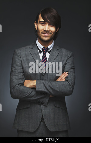 Portrait of happy young businessman smiling with his arms crossed. Handsome male executive standing with folded - Stock Photo