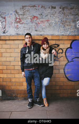 Full length portrait of handsome young man standing with his beautiful girlfriend leaning against a wall. - Stock Photo