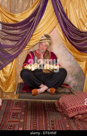 Sultan character greeting while sitting on a flying carpet - Stock Photo