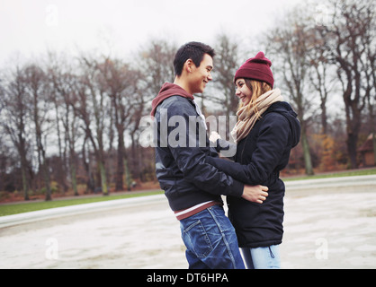 Handsome young man and beautiful woman standing together looking at each other smiling. Teenage mixed race couple - Stock Photo
