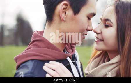 Closeup image of romantic young couple in park. Asian teenage couple about to kiss each other while outdoors on - Stock Photo