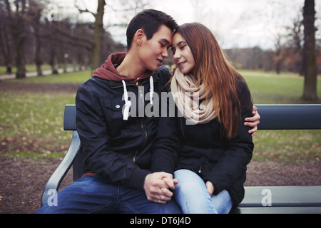 Young couple sharing a tender moment while sitting on a park bench. Teenage asian couple outdoors in park. - Stock Photo