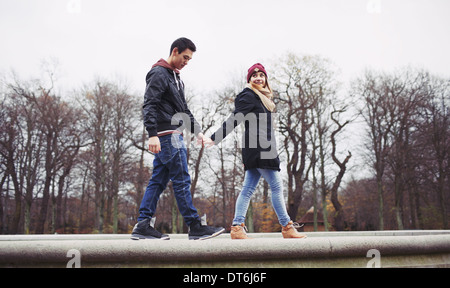 Low angle view of handsome young man with his girlfriend walking together holding hands in park. Mixed race teenage - Stock Photo