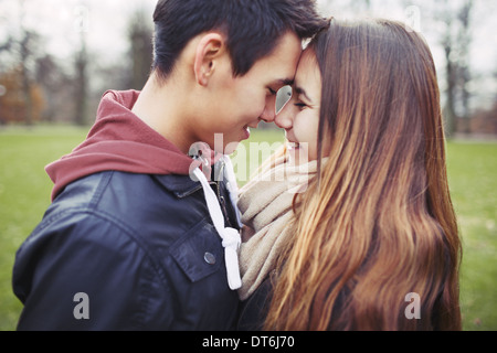 Close up of cute teenage couple in love sharing a special moment. Romantic young man and woman outdoors in park. - Stock Photo