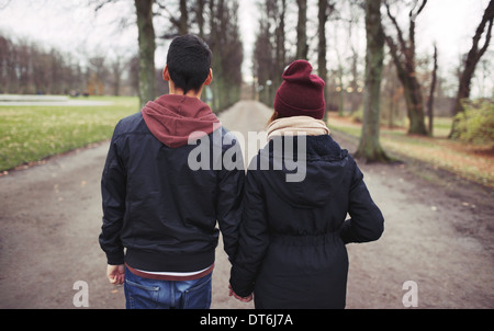 Rear view of teenage couple walking in park holding hands. Young man and woman in warm clothes outdoors. - Stock Photo