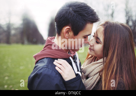 Teenage couple in romantic mood. Affectionate young couple in park. - Stock Photo