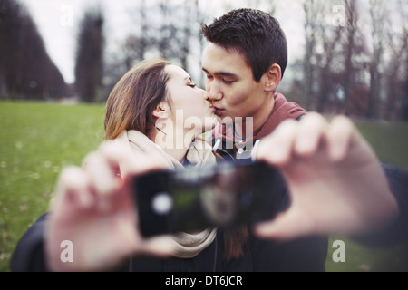 Lovely young couple taking self portrait while kissing at the park. Teenage boy and girl with smartphone outdoors. - Stock Photo