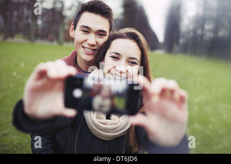 Young couple looking happy while taking pictures using a smart phone at the park. Teenage boy and girl in love photographing. - Stock Photo