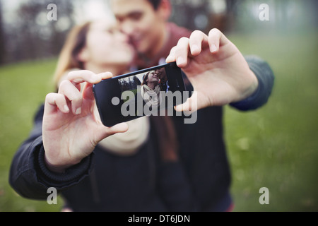 Romantic teenage couple taking self portrait with cell phone at the park. Young man and woman in love. - Stock Photo