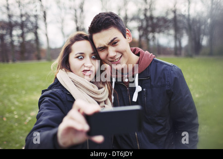 Funny teenage couple photographing themselves with smart phone in the park.  Cute young girl with her boyfriend - Stock Photo
