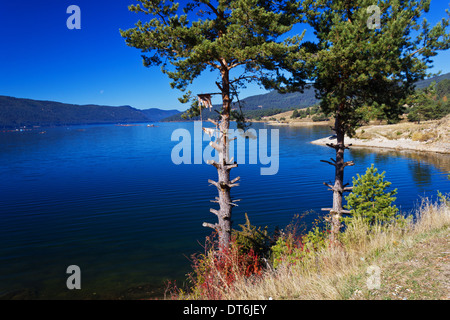 Mountain lake. A dam lake on the clear blue sky background. - Stock Photo
