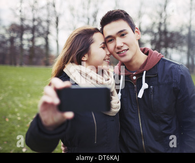 Affectionate young couple taking pictures using a smart phone at the park. Teenage boy and girl in love photographing - Stock Photo