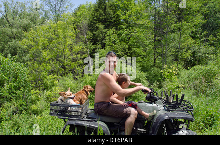 young father and son with two dogs on motorbike - Stock Photo