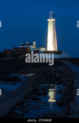 A view of St Mary's Lighthouse and causeway floodlit at dusk near Whitley Bay, Tyne and Wear - Stock Photo
