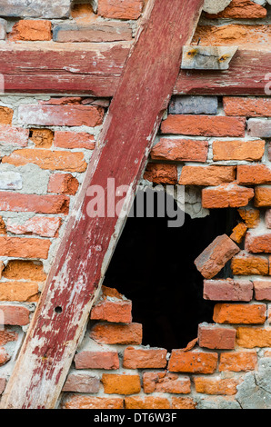 Black hole in a red brick wall - Stock Photo