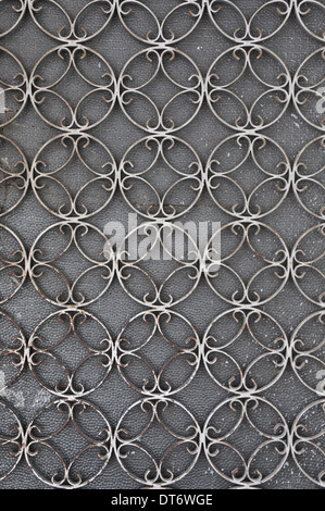 Vintage iron door frame with circles pattern detail and stained glass background. - Stock Photo