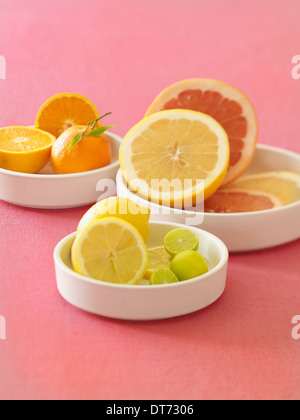 A white platter with oranges, blood oranges, grapefruit, lemon and limes on a pink fabric background. - Stock Photo