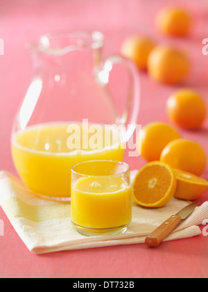 A glass pitcher of orange juice with a glass filled with fresh squeezed orange juice with several oranges in the - Stock Photo