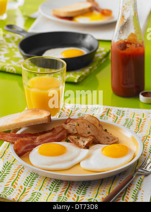A breakfast scene with sunny side up fried eggs, bacon, toast, breakfast potatoes, and a glass of orange juice - Stock Photo
